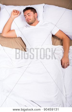 Birdseye view of an attractive man laying in bed