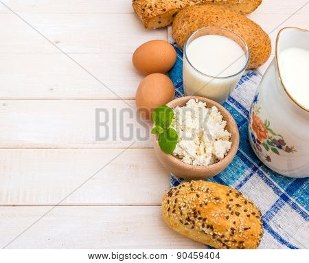 Breakfast of cheese, milk, bread and eggs on a light wooden background