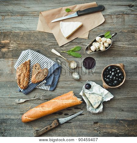 French cuisine. Different types of cheese, wine and other ingredients on a wooden table