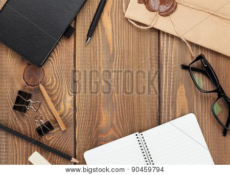 Office table with notepad, vintage envelope and supplies. View from above with copy space