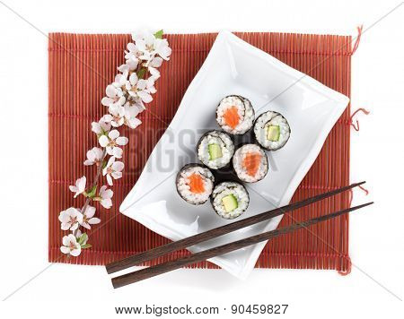 Sushi maki set with salmon and cucumber and sakura branch. Isolated on white background