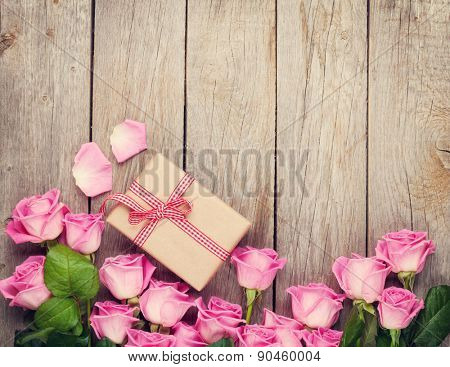 Pink roses and valentines day gift box over wooden table. Top view with copy space. Toned