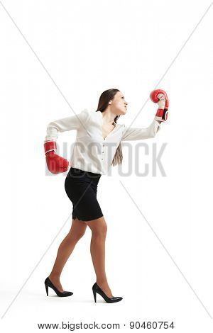 full length portrait of angry businesswoman in formal wear and red boxing gloves punching over light background