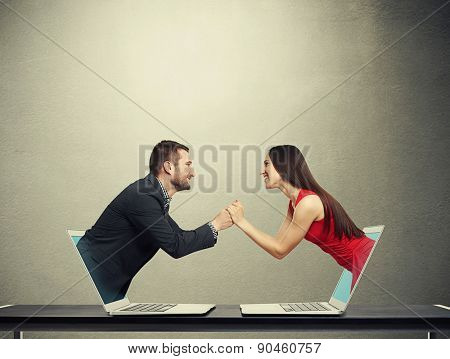 concept of love in social network. young man got out of the computer and holding hand of beautiful young woman who got out of another computer over dark background