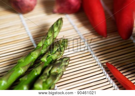 Asparagus on a mat with a red pepper.