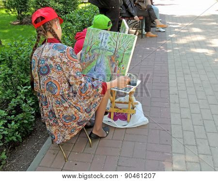 Young Women Artist Examines Painted Picture