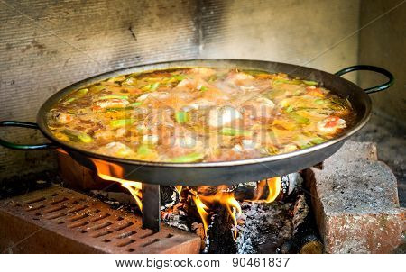 Cooking And Making A Traditional Spanish Paella Over Open Fire With Fire Wood And Coal