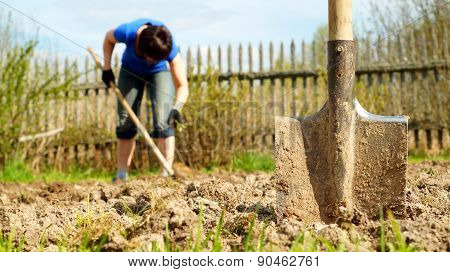 Spade sticking into the earth with a woman working on the background