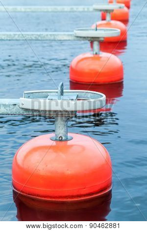 Red Mooring Buoys In A Row Floating On Blue Water