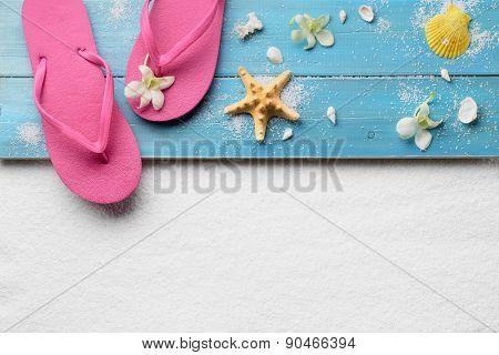 Flip-flops with seashells on sand beach