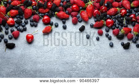 Fresh fruits - juicy strawberries and blueberries on stone background