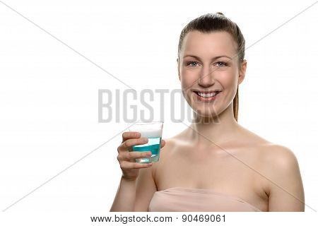 Smiling Young Woman Holding Mouthwash In A Glass