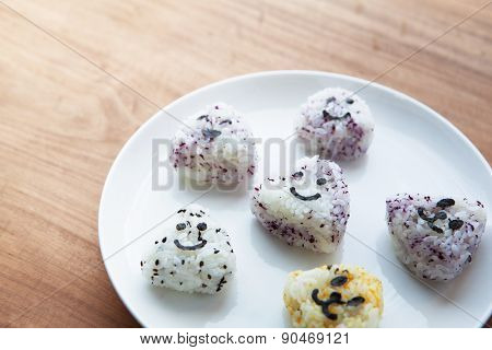 Onigiri rice balls on white plate, with smiley faces made with cut out nori seaweed. Shallow depth of field.