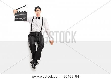 Cheerful male movie director holding a clapperboard and posing seated on a blank panel isolated on white background