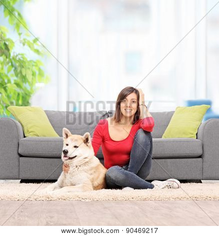 Young woman relaxing at home seated on the floor with her pet dog in front of a modern sofa shot with tilt and shift lens
