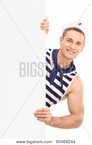 Studio shot of a cheerful young sailor posing behind a blank signboard isolated on white background