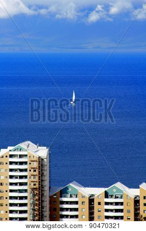 Sailboat floating away into the distance of the ocean