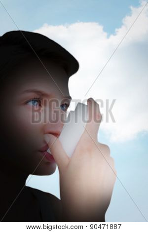 Blonde woman taking her inhaler against blue sky over green field