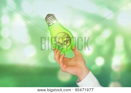 Hand presenting against light circles on green background
