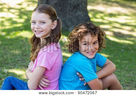 Little siblings smiling at camera on a sunny day