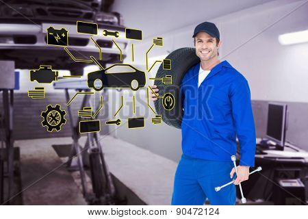 Confident mechanic carrying tire against auto repair shop