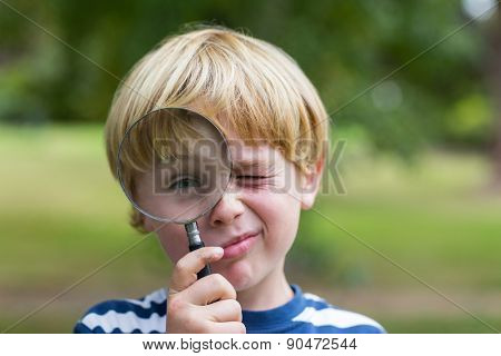 Curious little boy looking through magnifying glass on a sunny day