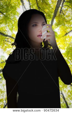 Asthmatic brunette using her inhaler against low angle view of tall trees