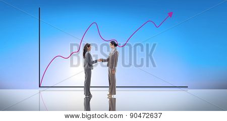 Businesswomen shaking hands against blue sky