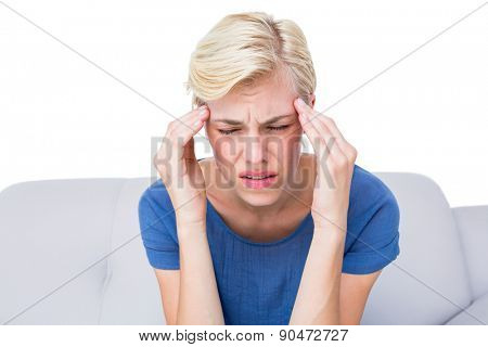 Attractive blonde woman having headache on white background