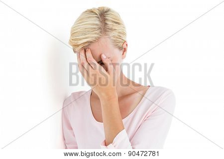 Nervous blonde woman covering her face on white background