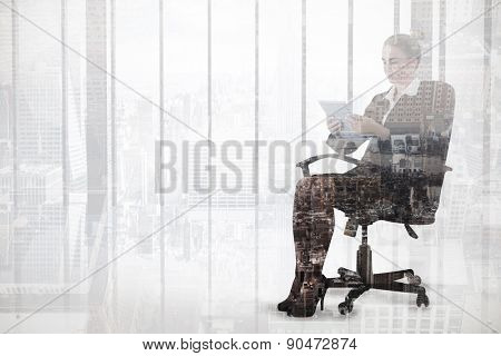 Businesswoman sitting on swivel chair with tablet against new york