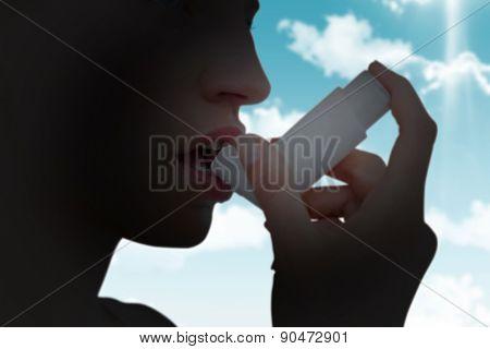 Blonde woman taking her inhaler against blue sky