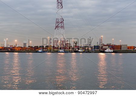 Port of Antwerp in the twilight with containers and tugs