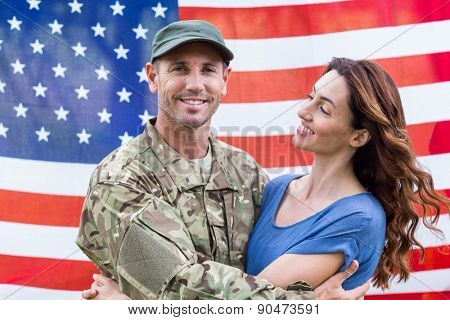 Handsome soldier reunited with partner against an american flag