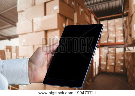 Man using tablet pc against shelves with boxes in warehouse