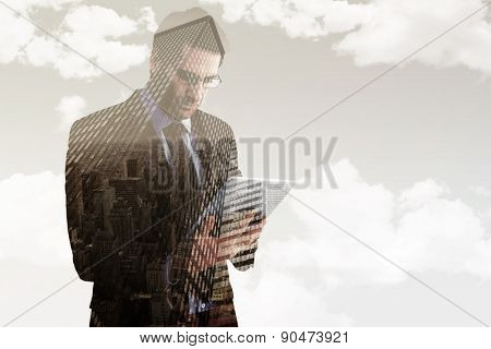 Businessman using a tablet computer against low angle view of skyscrapers