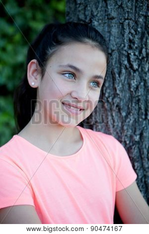 Happy preteen girl with blue eyes smiling at outside