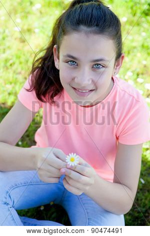 Happy casual preteen smelling a daisy at outside
