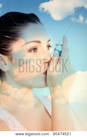 blue sky against woman with asthma using an asthma inhaler