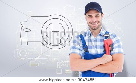 Confident young male repairman holding adjustable spanner against grey vignette