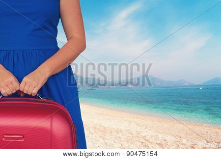 woman with luggage ob beach