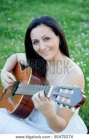 Brunette woman sitting on a flowered meadow playing guitar