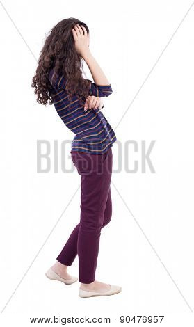 back view of standing young beautiful  woman.  girl  watching. Rear view people collection.  backside view of person.   woman in red jeans thoughtfully scratching his curly hair.