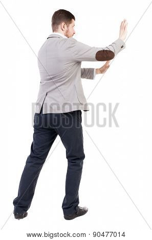 back view of business man pushes wall. Isolated over white background. Rear view people collection. backside view of person.  a bearded man in a jacket ran into an obstacle.