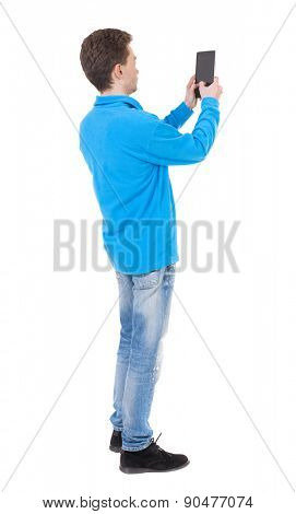 back view of standing young man with tablet computer in the hands of. Rear view people collection.  backside view of person.  Isolated over white background. guy in the blue sweater pictures of tablet