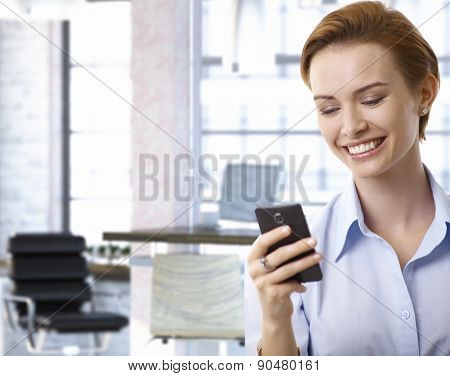 Closeup portrait of young businesswoman using mobilephone at office, smiling.