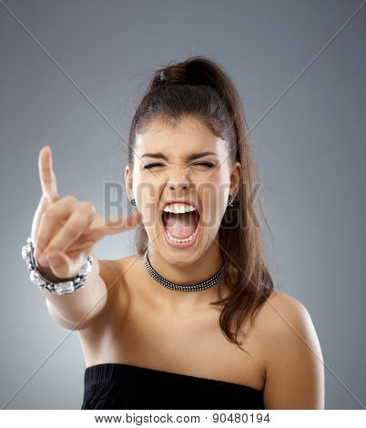 Provocative girl shouting eyes closed, showing rock on hand gesture.