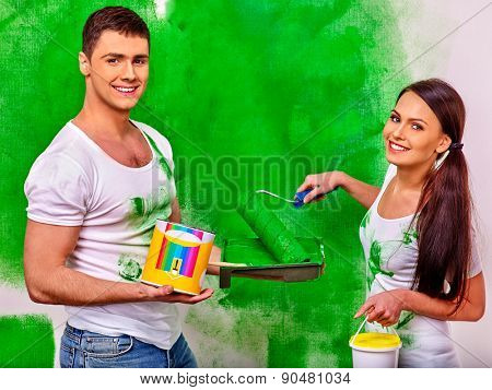 Happy young family paint wall at home.