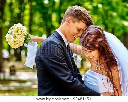 Bride and groom with flower summer huging  outdoor.