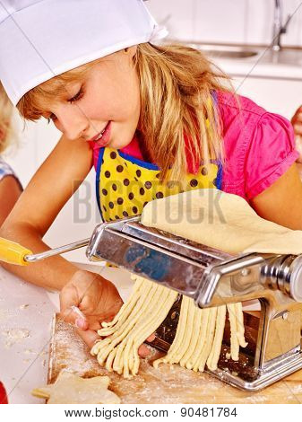Child in hat making homemade pasta at kitchen.